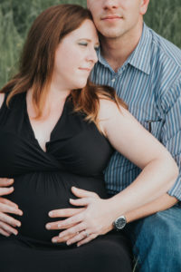 Tallahassee Maternity Photographer mom and Dad sitting down with hand on belly