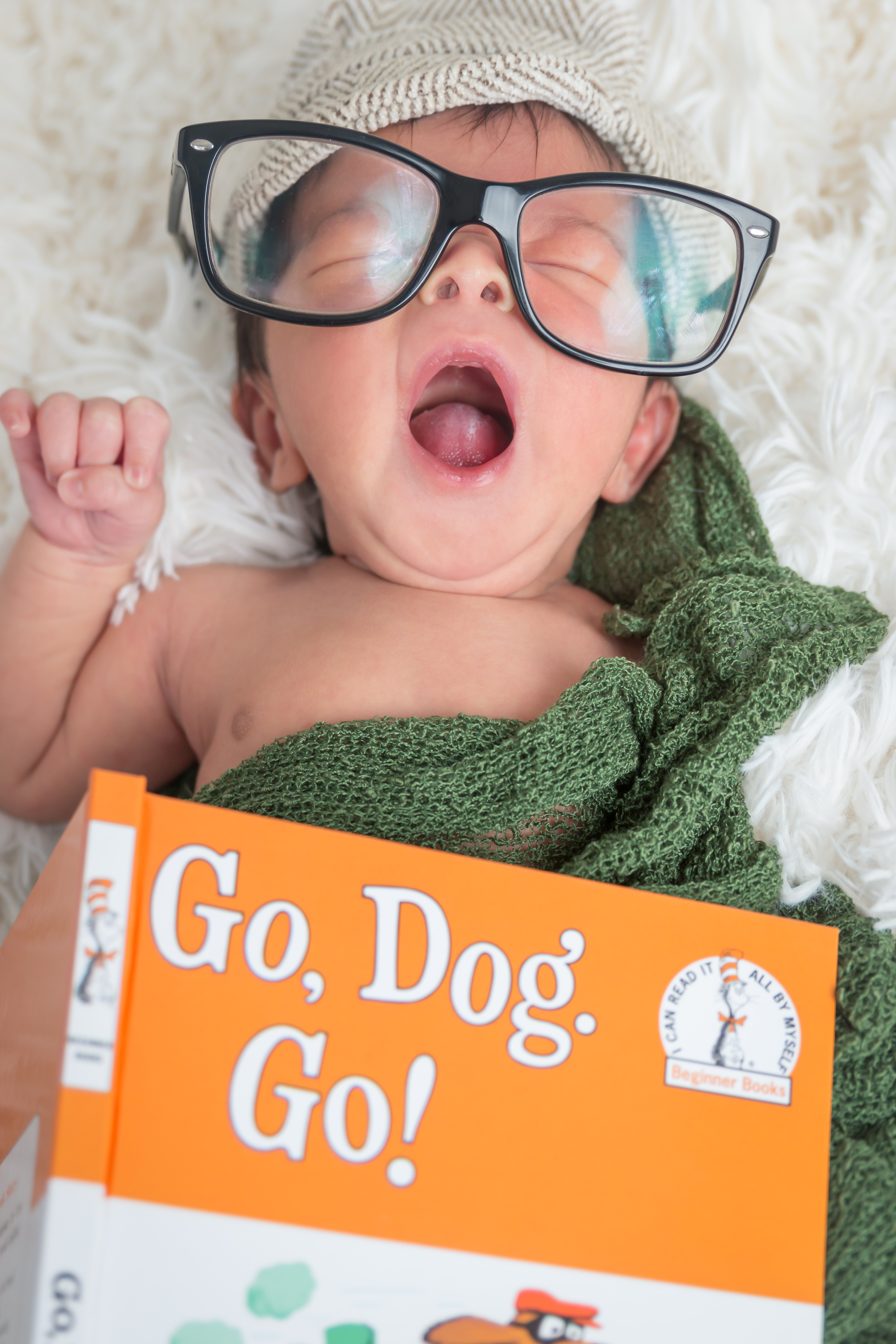 Baby yawning with gasses and a book Tallahassee newborn photographer