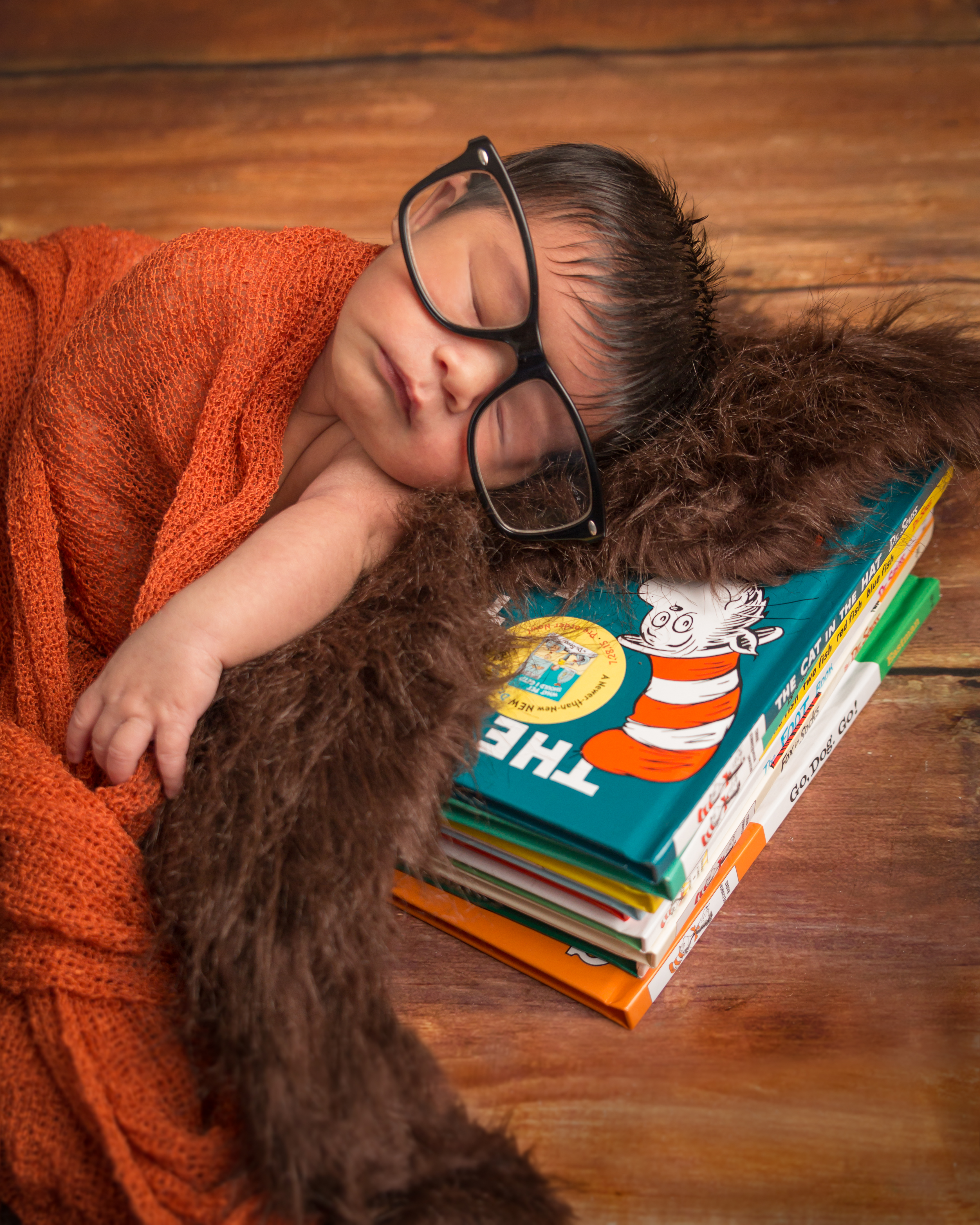 Baby sleeping on a bear skin rug with books and a glasses