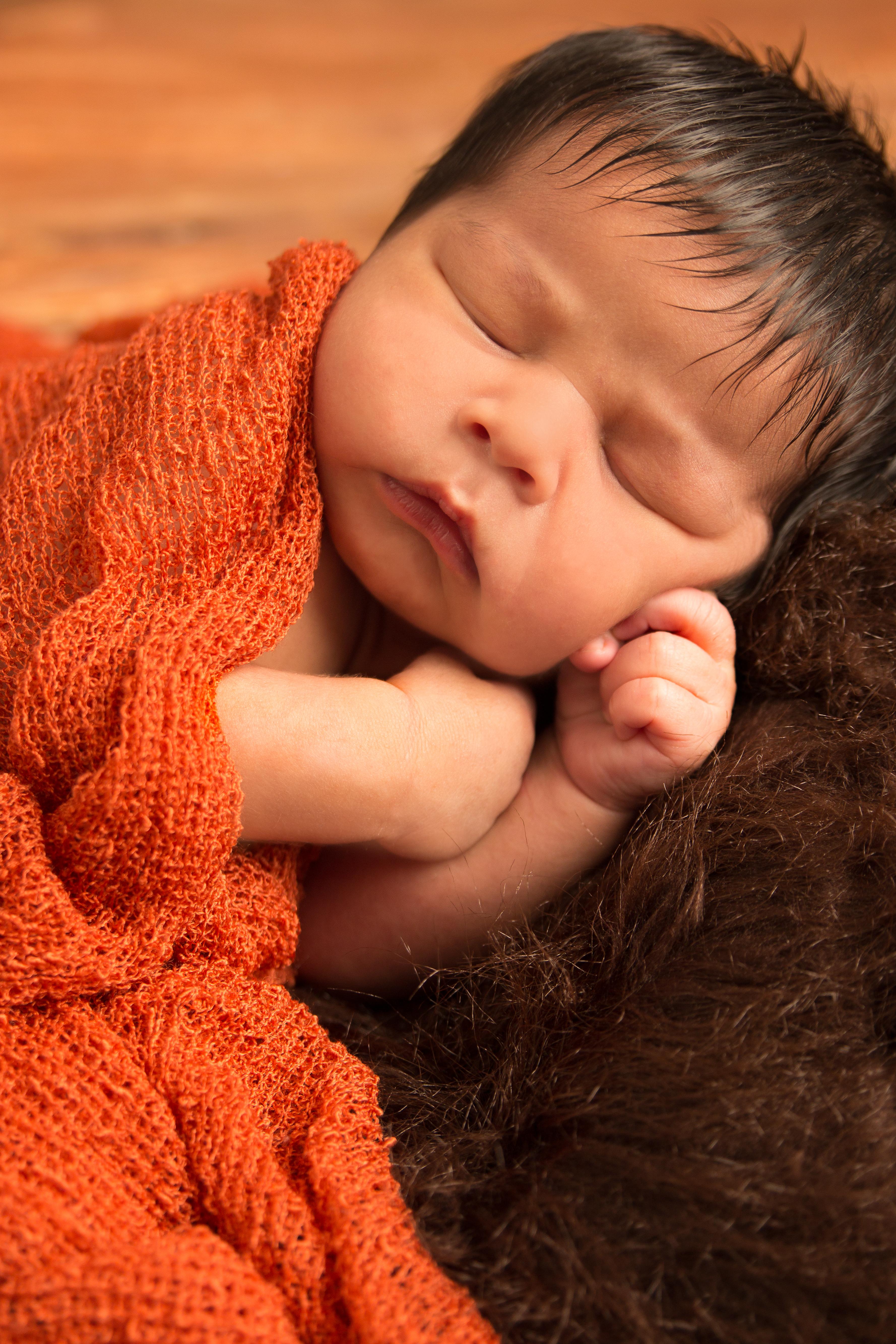 Baby sleeping on bear skin rug