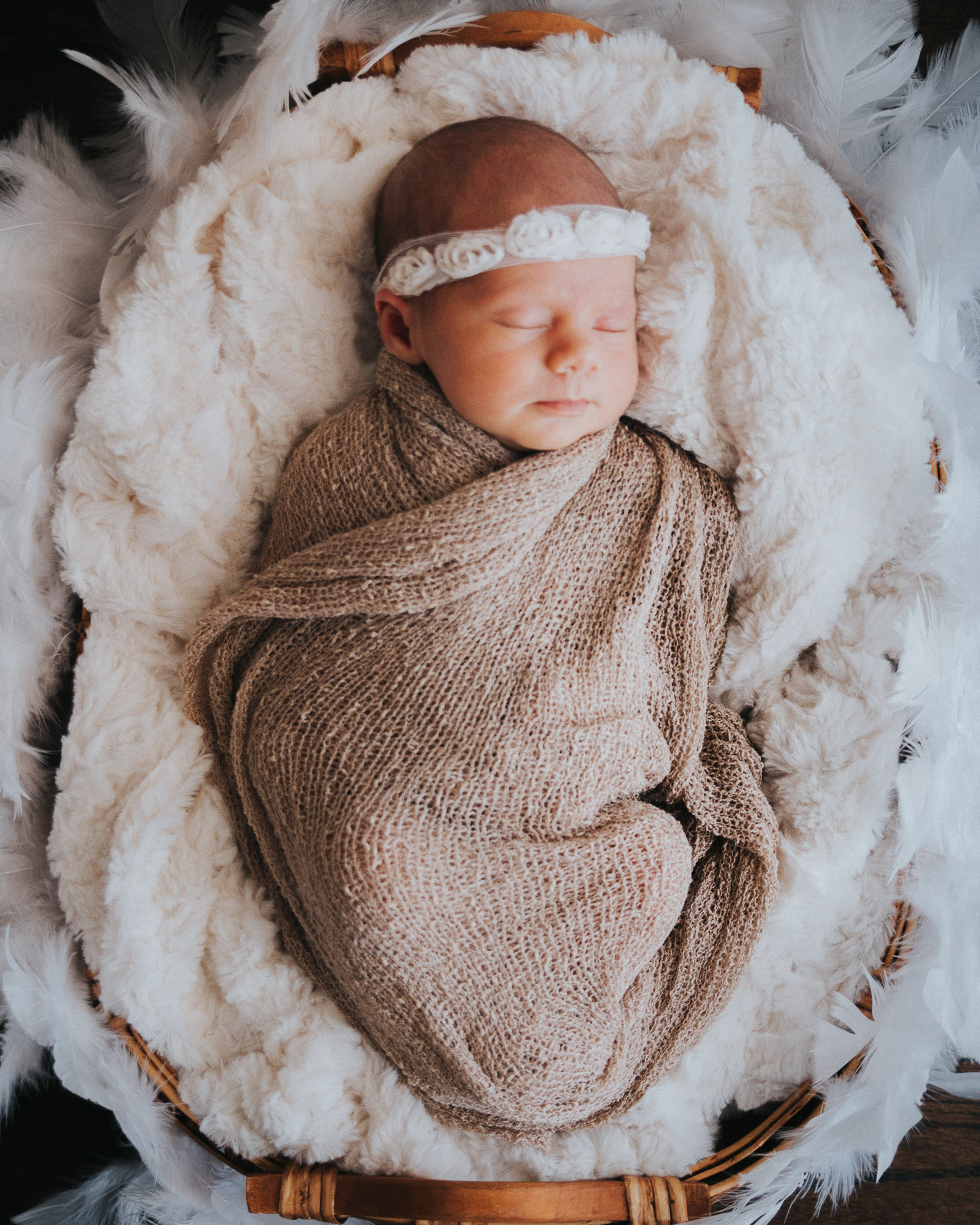 Newborn photographer on location in home Baby with headband on feathers