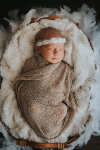 Newborn photographer on location in home Baby with headband on a bed of feathers